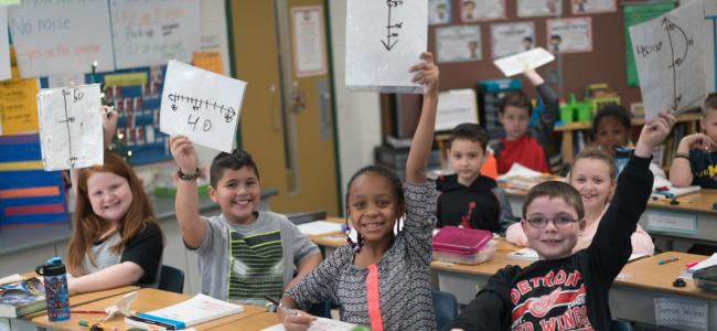 Students holding up math formulas
