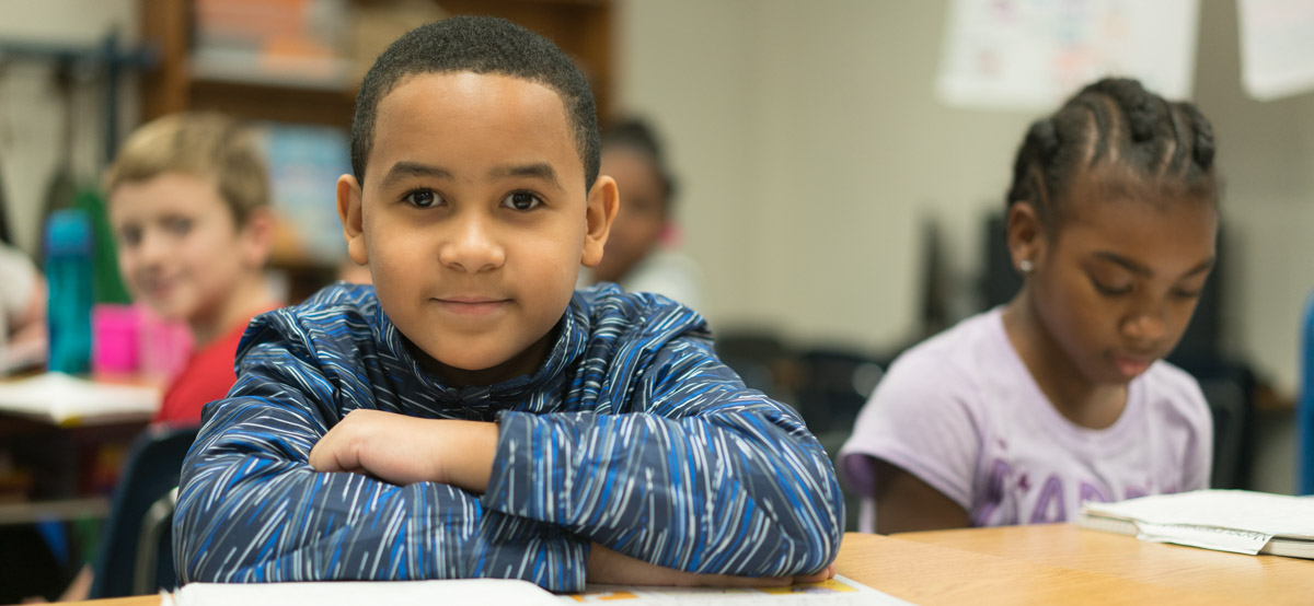 Boy in classroom looking at camera