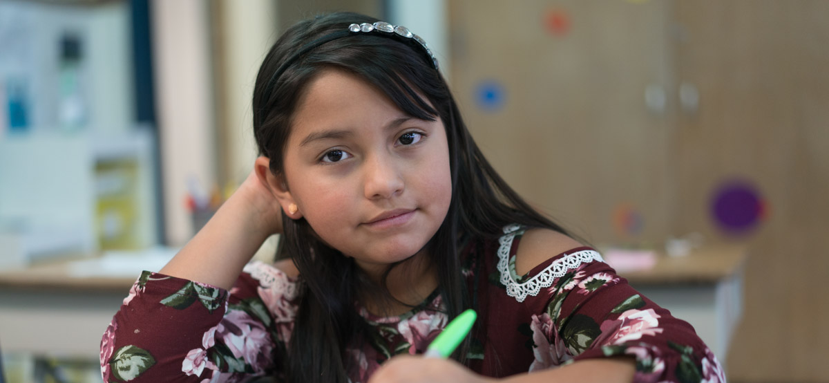 Girl in classroom looking at camera