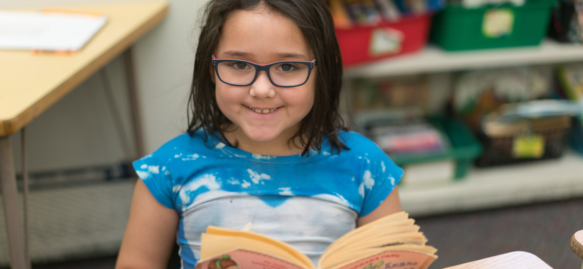 Girl reading a book at Roosevelt elementary