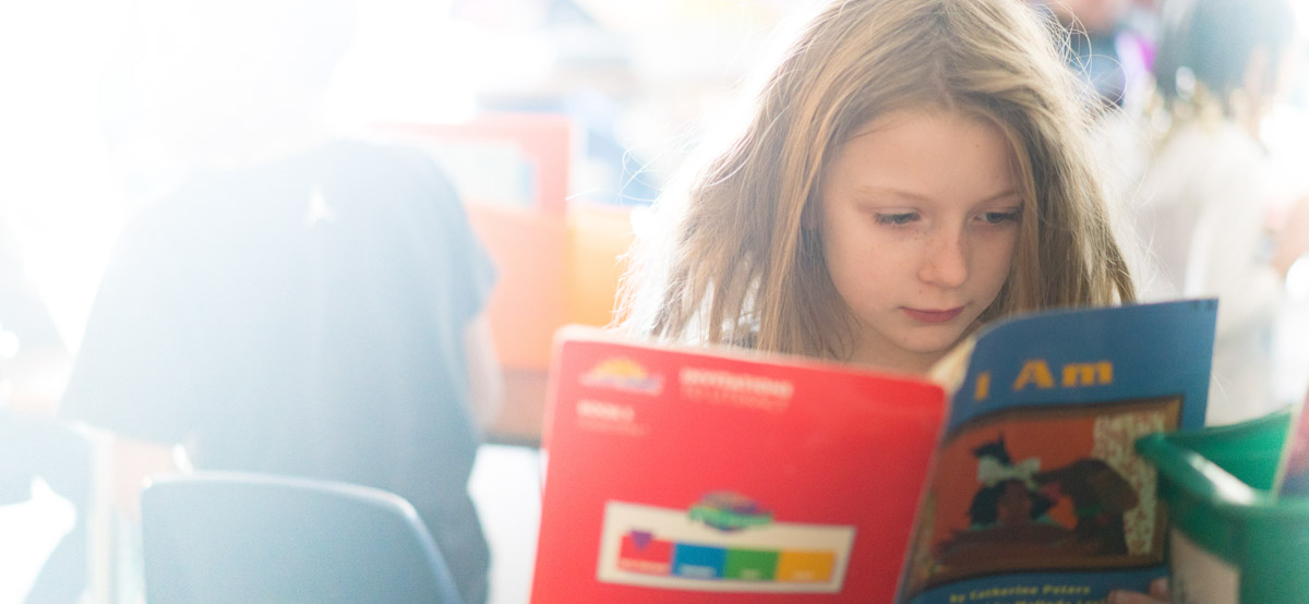 Girl reading a book in class 1
