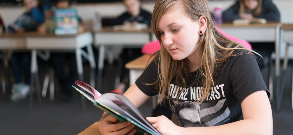 Student reading a book in class