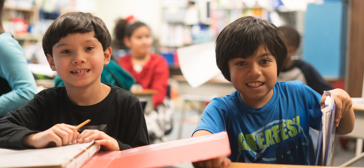 Two students in classroom smiling for camera 2